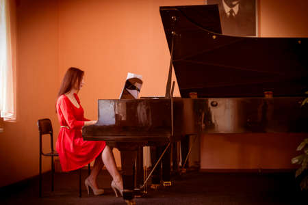 Woman in red dress playing grand piano Stock Photo