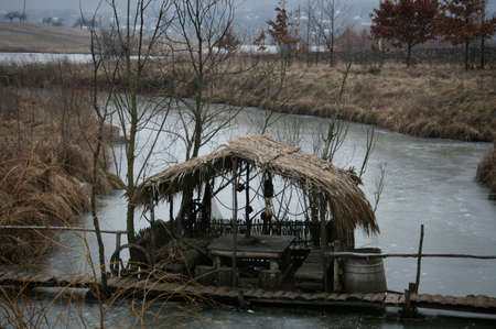 pergola: Old pergola covered with reeds on the bridge over frozen river Stock Photo