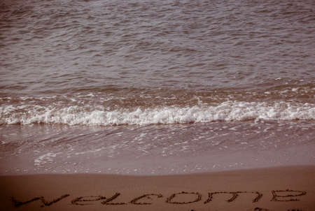 homecoming: Welcome written in a sandy beach