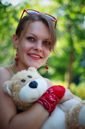 no name: Young woman holding a teddy bear (no name or trademark) in park. Shallow depth of field.