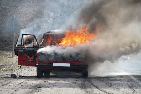 Burning car on desert rural road Фото со стока