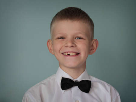 toothless: A young toothless boy wearing white shirt and black bow tie