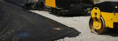 blacktop: Industrial pavement truck laying fresh asphalt on construction site