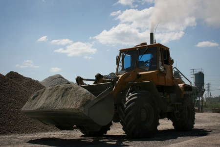 backhoe loader: Wheel loader excavator with backhoe unloading gravel