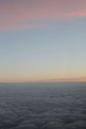 stratus: Aerial view of a cloudy sunrise while flying above the clouds