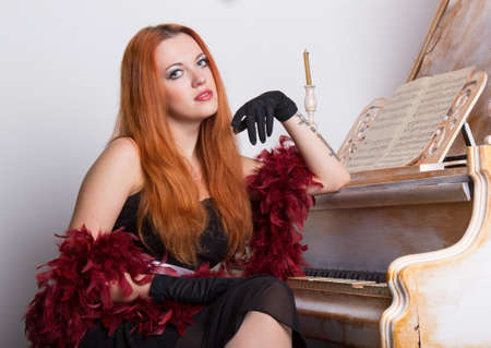 black boa: Red-haired woman in a black dress and boa sitting next to a piano.