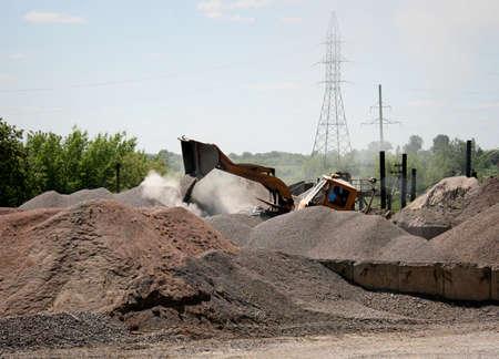 wheel loader: Wheel loader excavator unloading gravel on construction site Stock Photo