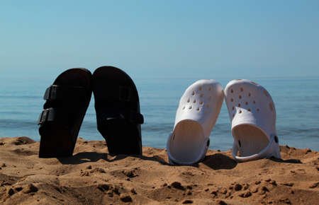 flip flop: Dark and light flip flop on beach in sand against sea Stock Photo