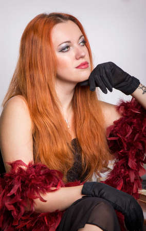 black boa: Red-haired woman in a black dress and boa Stock Photo