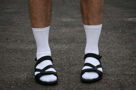 The lower part of men's feet in white socks and sandals