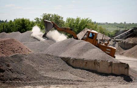 unloading: Wheel loader excavator unloading gravel on construction site Stock Photo