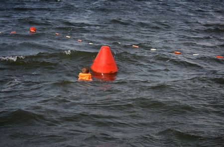 lifejacket: Little child in the life jacket swimming to buoy Stock Photo