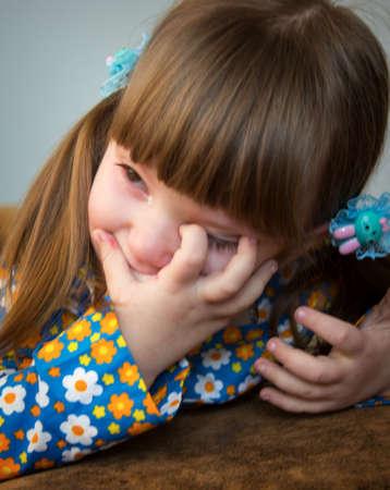 ojos llorando: Una ni�a frot�ndose los ojos llorosos