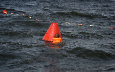 lifejacket: Little child in the life jacket near buoy