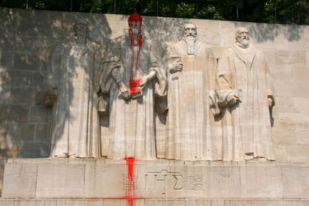 Reformation wall in Geneva, Switzerland. Sculptures of the four great figures of the geneva protestant movement. Statue of John Calvin pour paint.