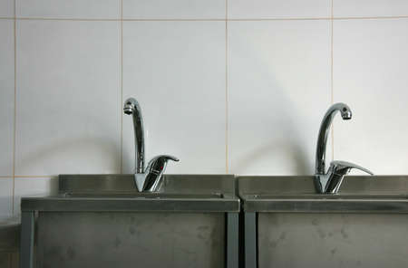 basins: A photo of taps connected to two stainless steel basins on a beige work wall
