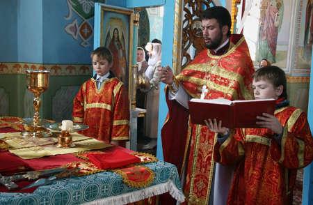 sotana: LUTSK, UKRAINE - NOVEMBER 02 - Orthodox priest and little sextons during holiday prayers in Lutsk on November 02, 2008. Editorial