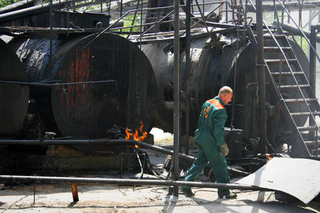 inflammable: LUTSK, UKRAINE - JUNE 02 - The worker near the tank of production plant asphalt  in Lutsk on June 02, 2008. Editorial