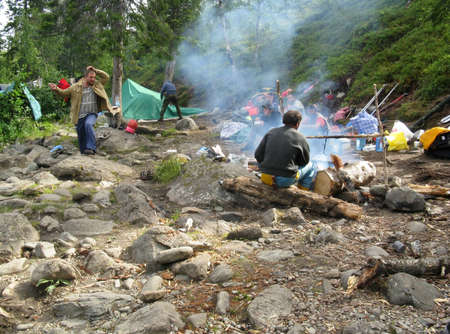 camping pitch: KOLA PENINSULA, RUSSIA - AUGUST 10 - A group of tourists set up a tent in the woods and cook a meal on a campfirer in Kola Peninsula on August 10, 2008. Editorial