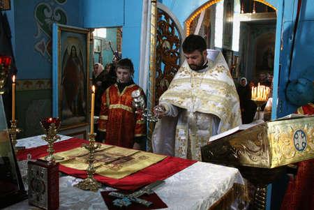 cassock: VOYUTYN, UKRAINE - JANUARY 08: Orthodox priest and little sexton during Christmas service in Voyutyn on January 08, 2009.