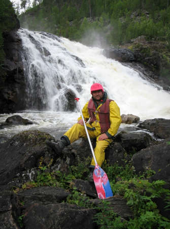 life jacket: BUG, UKRAINE - AUGUST 13 - A man in a life jacket and a paddle near a waterfall in Bug on August 13, 2008