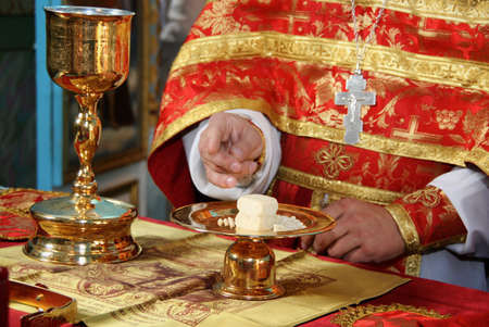 Hands of priest consecrates bread during orthodox liturgy ceremony Editorial