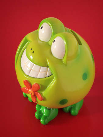 money box: Plastic green frog with flower as money box on a red background