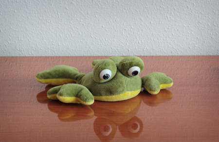 softy: Plush toy frog lying at the table. Shallow depth of field.