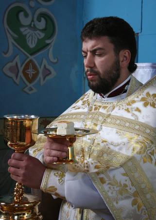 liturgy: LUTSK, UKRAINE - JANUARY 08 - Priest consecrates bread during orthodox liturgy ceremony in Lutsk on January 08, 2009.