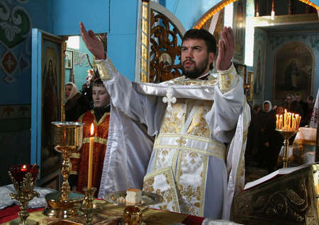 liturgy: VOYUTYN, UKRAINE - JANUARY 08 - Priest consecrates bread during orthodox liturgy ceremony in Voyutyn on January 08, 2009.