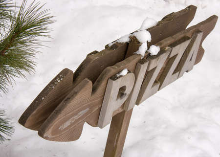 Wooden pointer in the shape of the arrow with the word pizza on a snow background