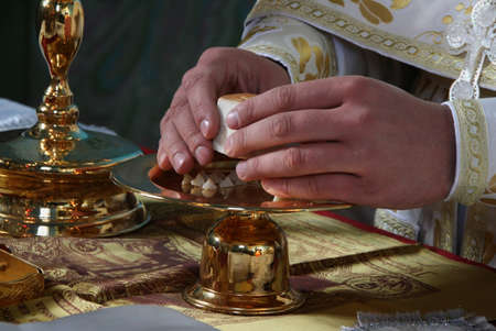 liturgy: Hands of priest consecrates bread during orthodox liturgy ceremony Stock Photo