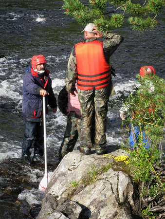 protective helmets: KOLSKYY, RUSSIA - 11 AUGUST 2008 - Men in protective helmets and life jackets on the rock near river.