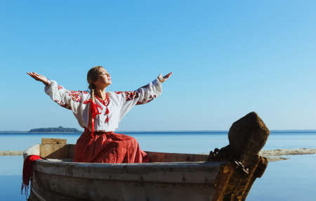 outspread: Happy carefree caucasian woman in ukrainian embroidered shirt in boat in glow of sun with arms outspread and face raised in sky enjoying open spaces on lake, serenity in nature.