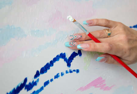 Hand with brush and paint Stock Photo
