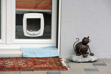 Interlaken, Switzerland - May 04, 2009: A regular pet flap on a glass door and metal statue of a cat on a stone in Interlaken, Switzerland. Stock Photo