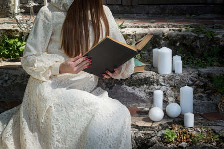 Woman in the style of Gothic sit on staircase and read book