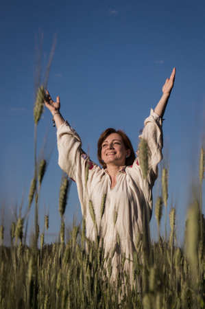 beatitude: Caucasian woman in a linen shirt standing with raised hands at a wheat field