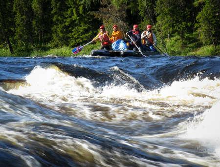 threshold: KOLA PENINSULA, RUSSIA - 16 AUGUST 2008: Four men on an inflatable catamaran  overcome the threshold of the turbulent river Editorial