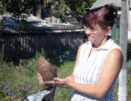 KRASNY LIMAN, UKRAINE - 06 SEPTEMBER 2014: A woman holds the remains of an artillery shell that destroyed her home after the bombing separatists in the village Krasny Liman Donetsk region