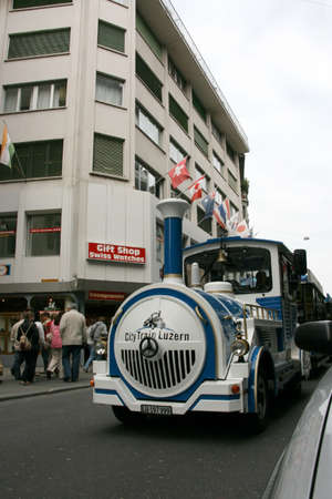 trackless: LUCERNE, SWITZERLAND - MAY 05, 2009: Blue and White Trackless Train travels through the streets of the city providing a convenient way for tourists to see variety of sightseeing attractions