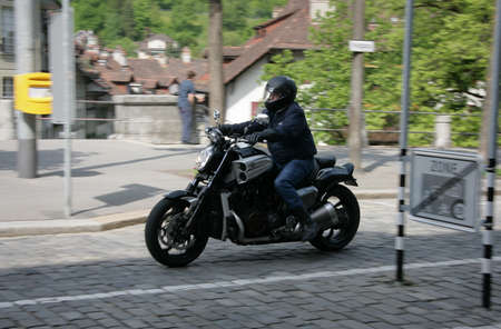 slow motion: BERN, SWITZERLAND - 03 May 2009: Unknown man riding a motorcycle on the street with blur movement