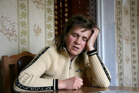 RIVNE, UKRAINE - 24 October 2008: Woman sitting at the table in a depressed state