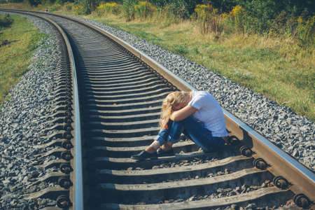 Depressive woman sitting on a railway track Stock Photo