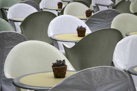 Outdoor summer restaurant tables and chairs with flowers in pot