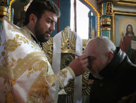 VOYUTYN, UKRAINE - 08 January 2009: Orthodox priest commits the ceremony of the anointing at the celebration of a Christmas in the church