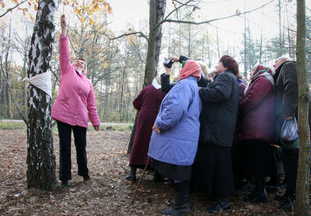 pagan cross: RIVNE, UKRAINE - 21 October 2008: Woman filmed on camera tree which was a religious sign Editorial
