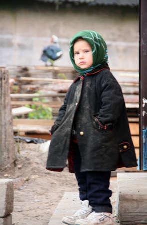 RIVNE, UKRAINE - 04 NOVEMBER 2008 - Poor little boy stand near home after fire Editorial