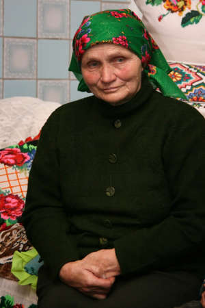 VOLODYMYREC, UKRAINE - 03 November 2008: Senior woman sits on bed with embroidered pillows in rural parlor