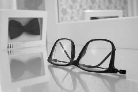 Mens accessories eyeglasses and bow tie near mirror. Shallow dept of field.